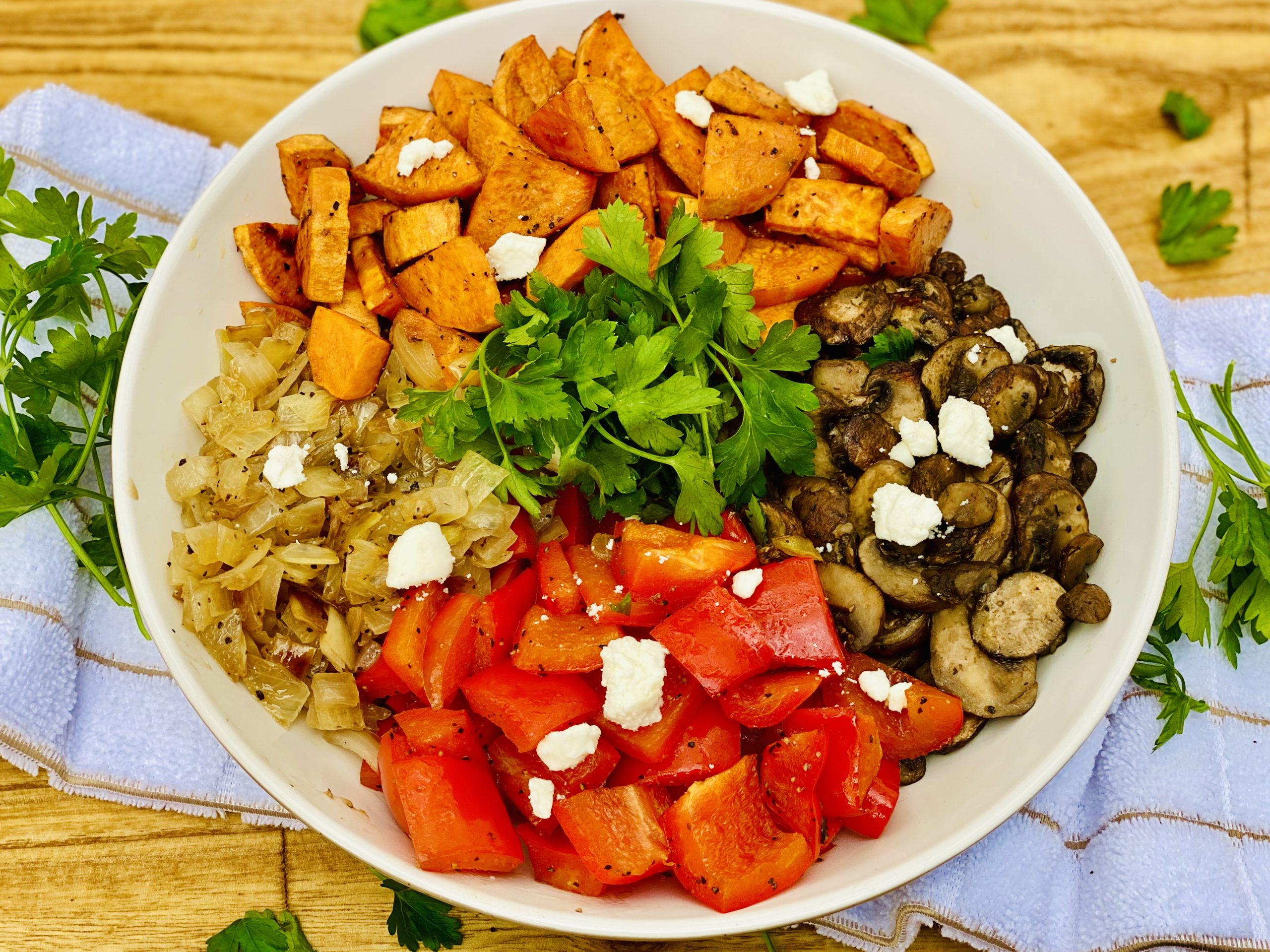 red peppers, sweet potatoes, mushrooms, and onions in white bowl sitting on top of a white towel