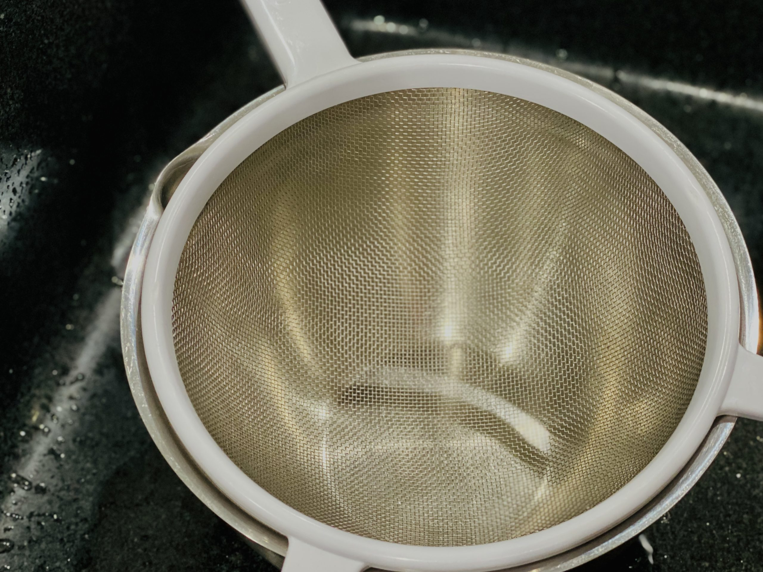 Strainer inside a bowl in a sink.