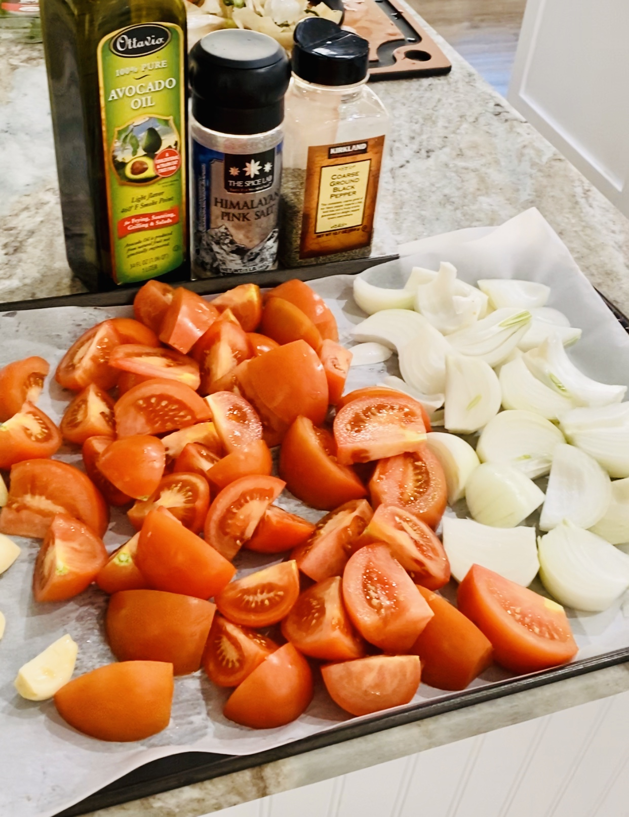 Sliced veggies with oil and spices on a counter.