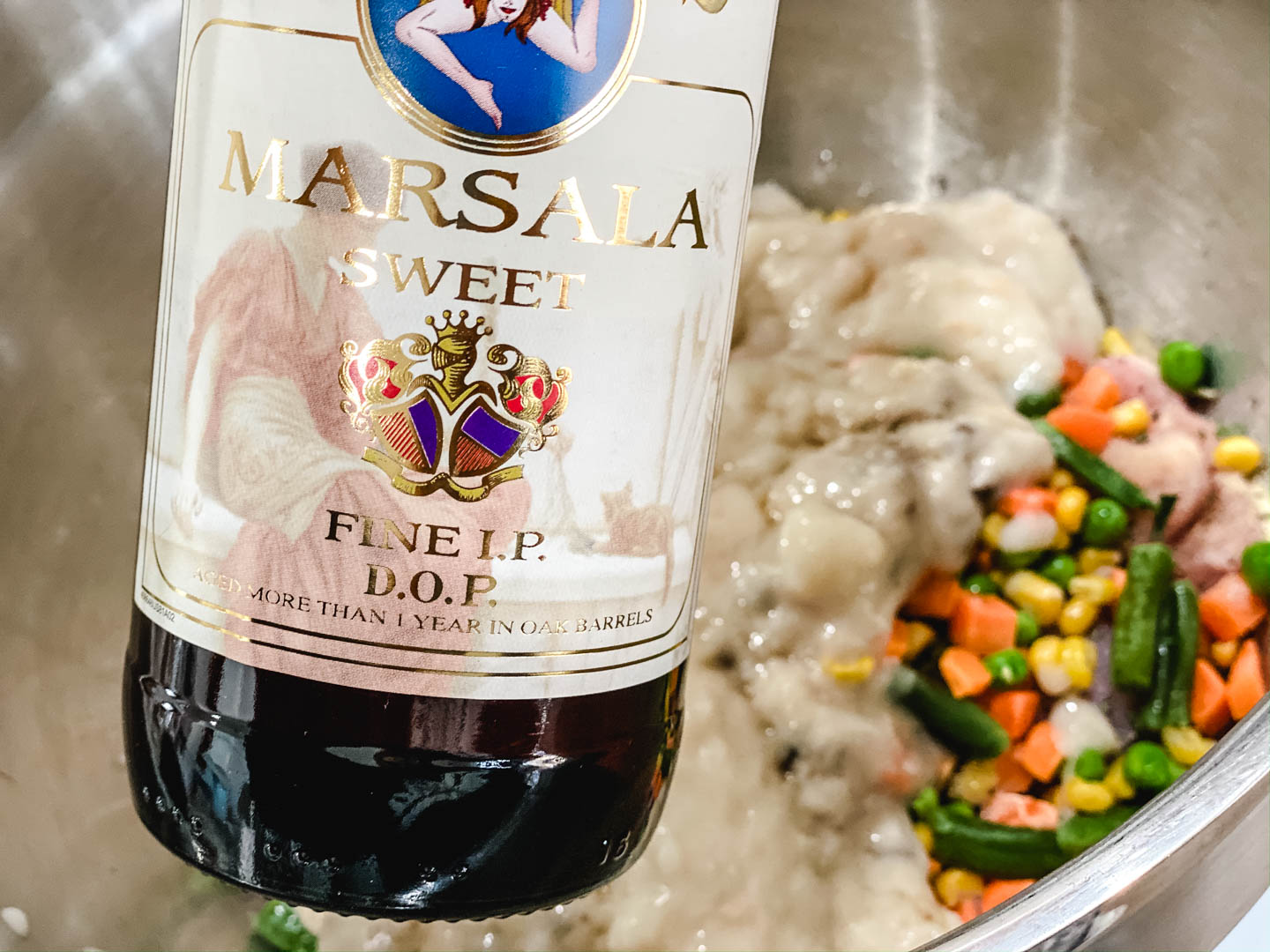 Bottle of marsala wine with chicken, veggies and soup in the background