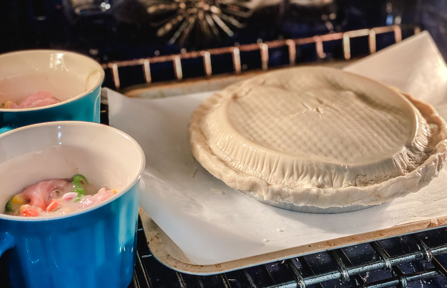 uncooked chicken pot pie in the oven with 2 blue mugs with gluten free chicken pot pie filling