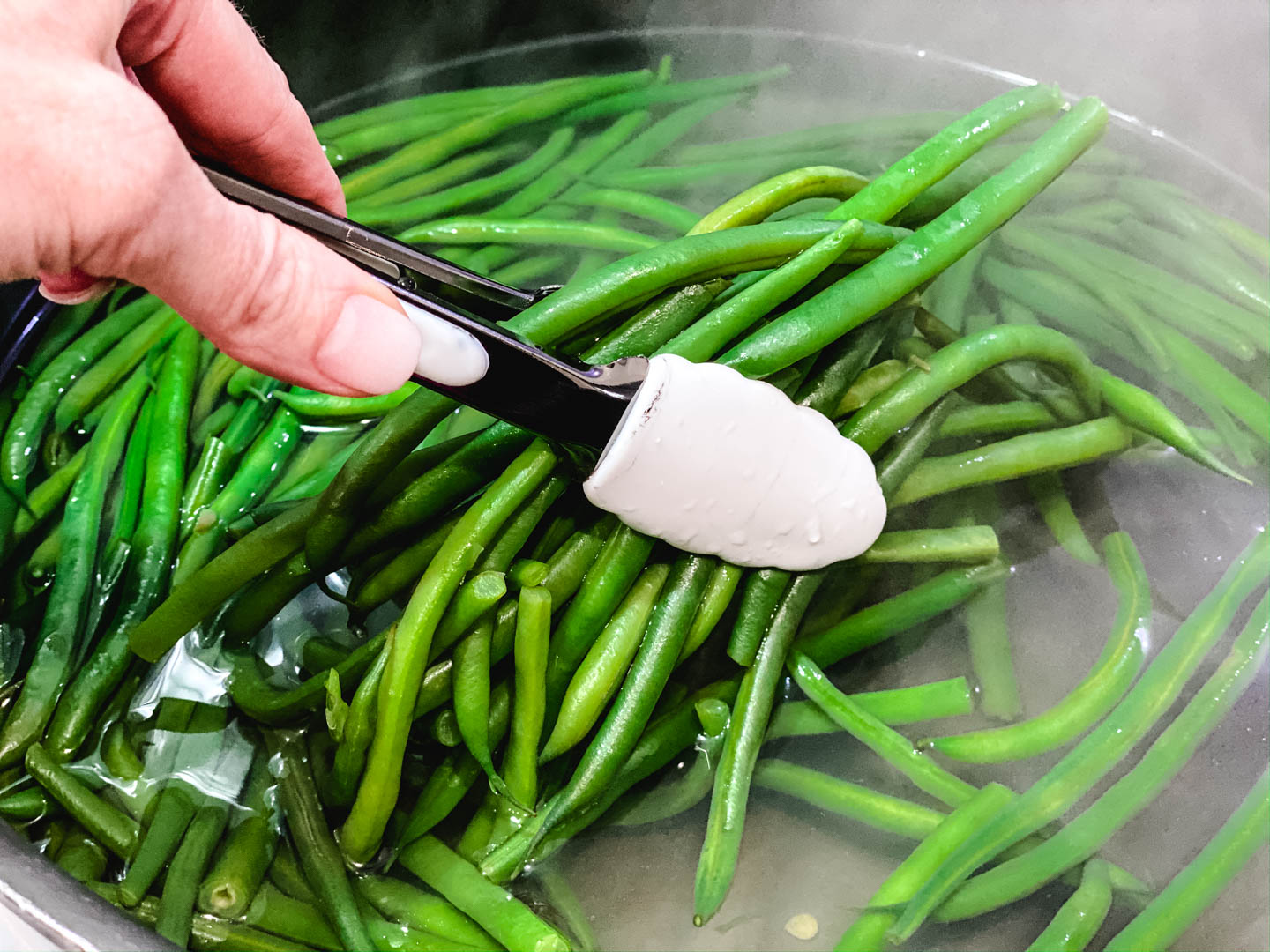 steamed green beans with a person holding white thongs.