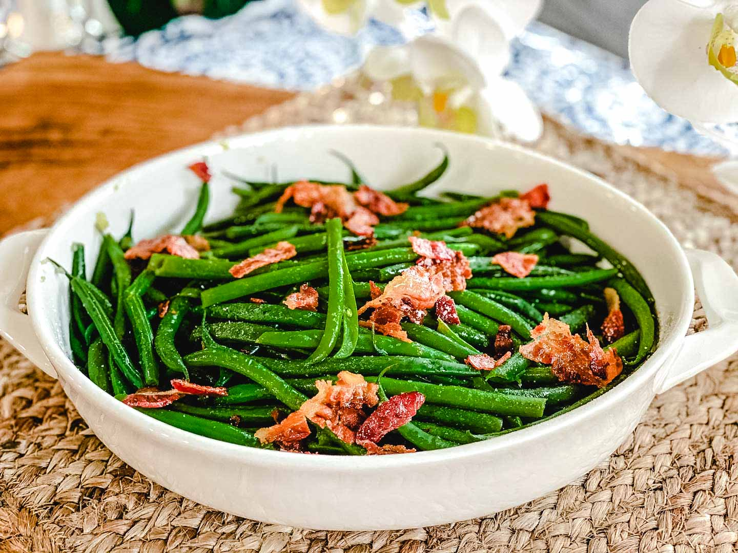 green beans with bacon in a white bowl on top of a brown board.