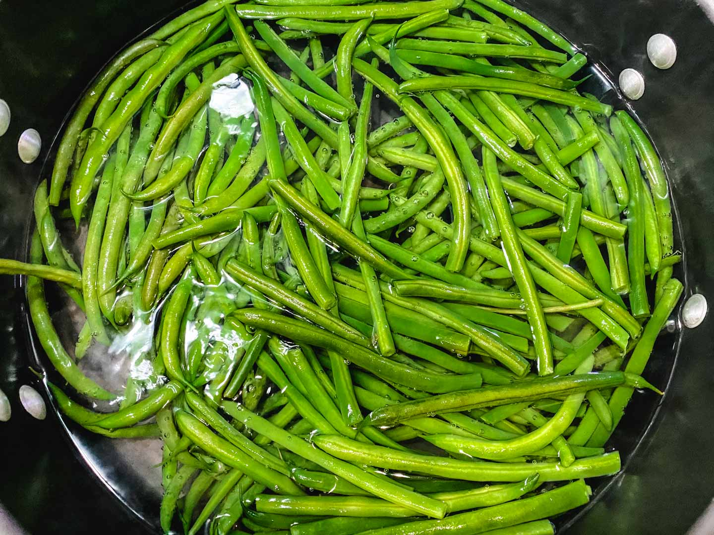green beans sitting in water in a black pot.