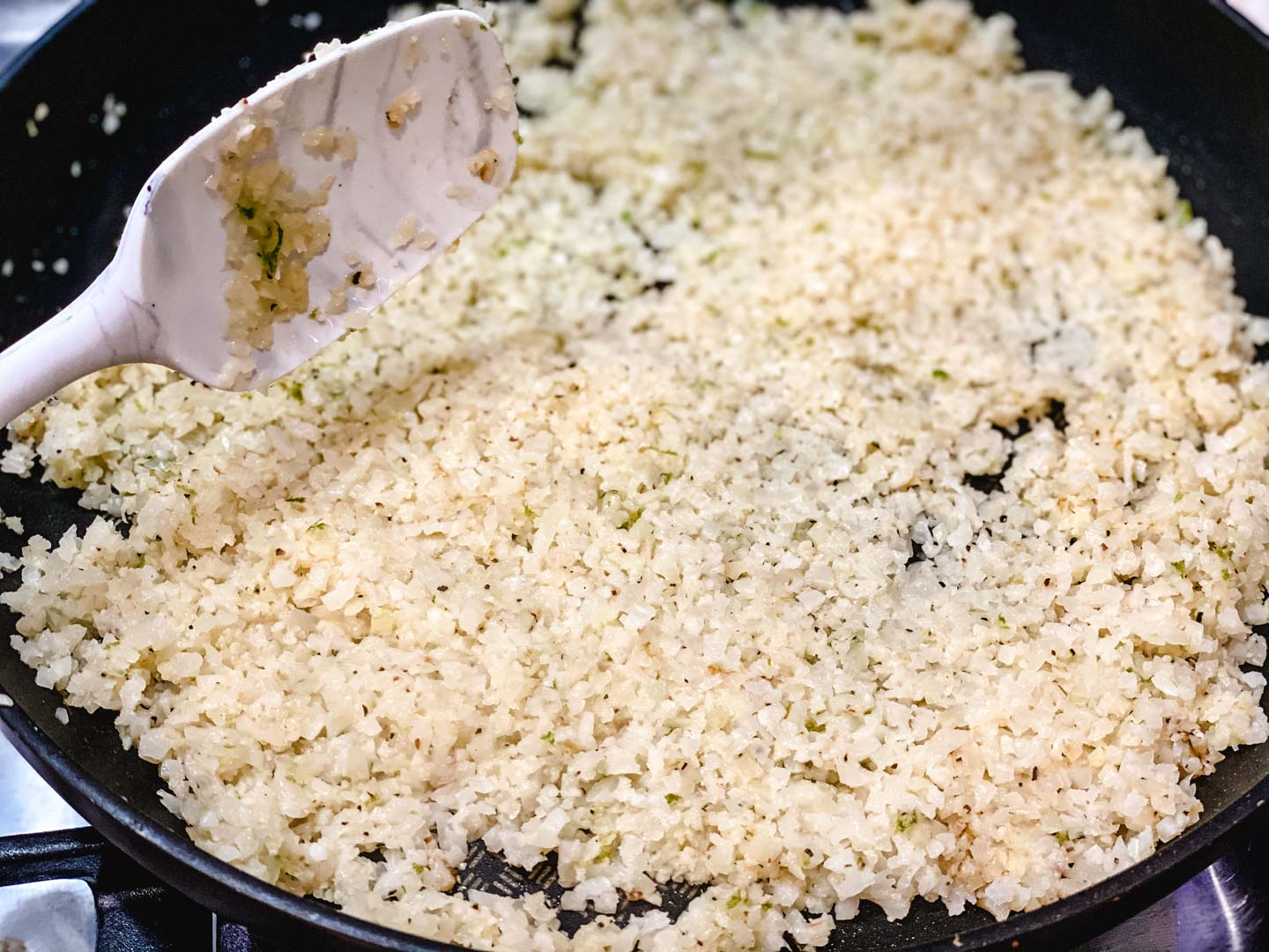 cauliflower rice in a black skillet with a white spoon