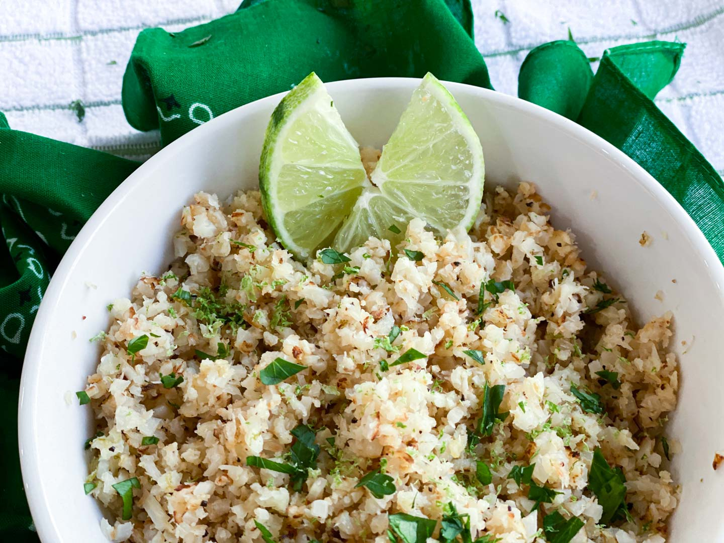 Cauliflower rice in a white bowl on a green towel with parsley