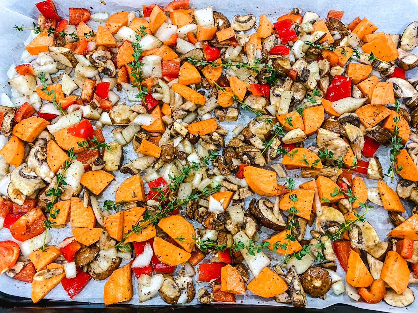 onions, red peppers, sweet potato, mushrooms, and fresh thyme on a baking sheet