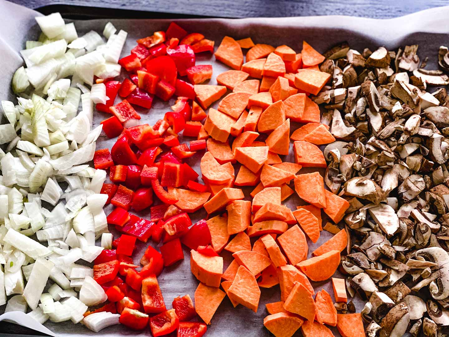 onions, red peppers, sweet potato and mushrooms on a baking sheet