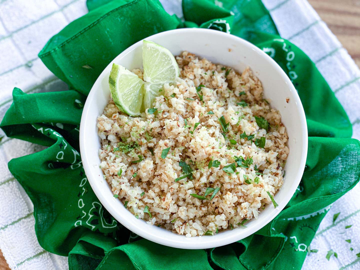 Cauliflower rice in a white bowl with a green napkin.