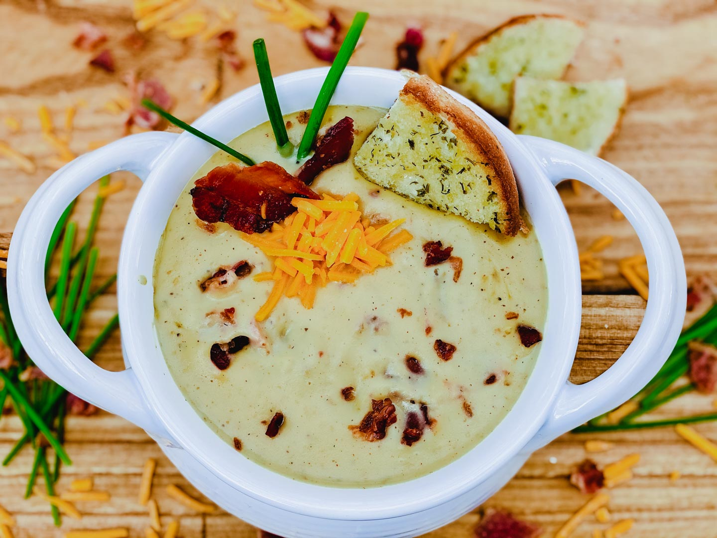 Potato soup in a white bowl with bacon and chives on a wood board.
