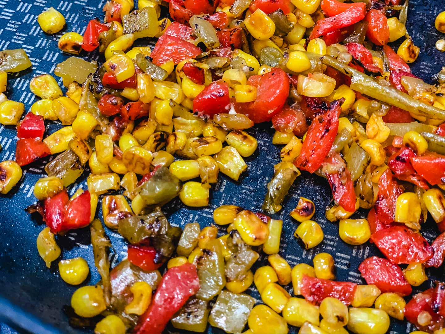 roasted corn, roasted red peppers and green chilis in a skillet.