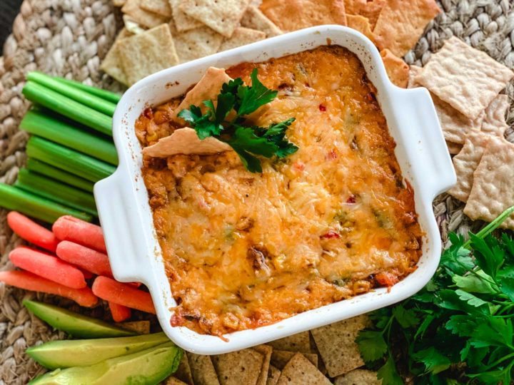 Pimento cheese dip in a white bowl with parsley, carrots, celery, avocado and crackers.