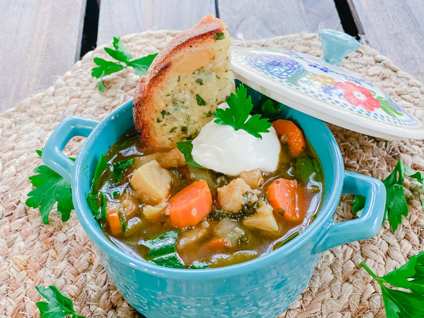 Vegetable soup with carrots, potatoes, green beans, spinach with a dollop of sour cream in a blue bowl.