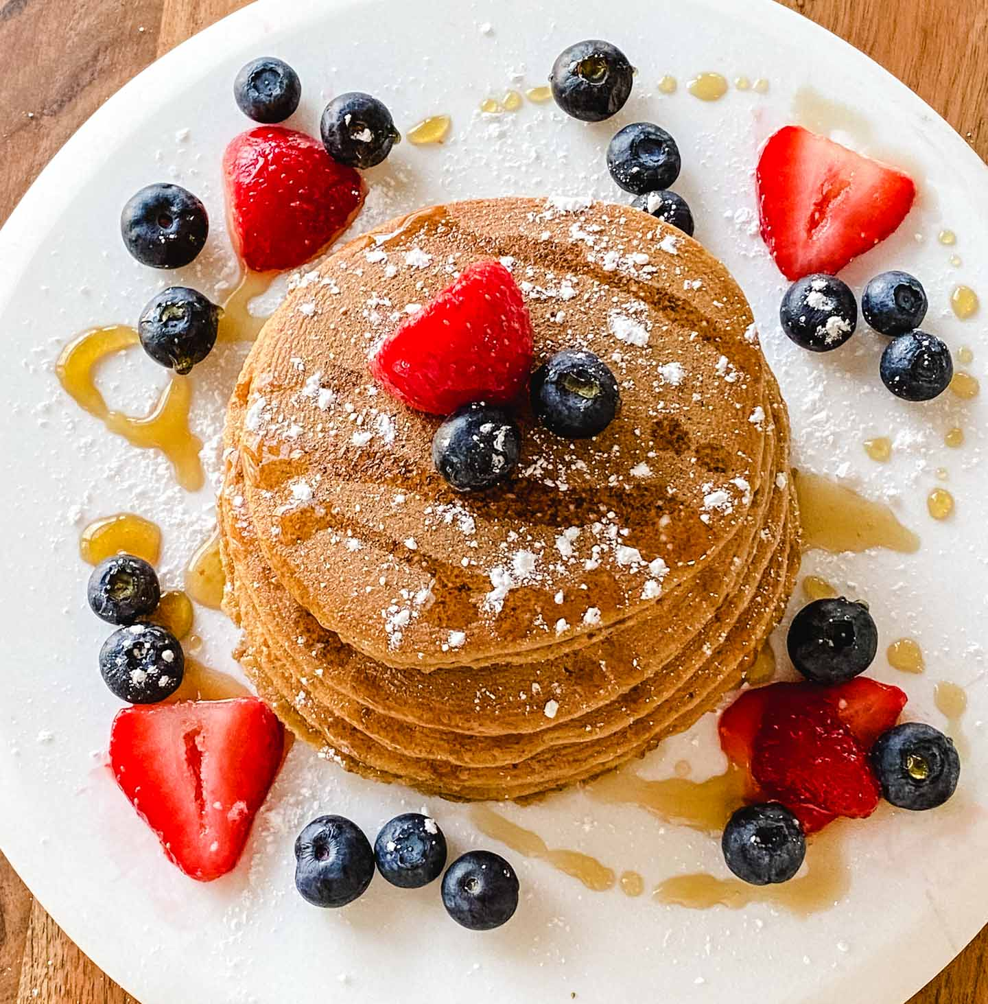 Pancakes on a plate with stawberries, blueberries, powdered sugar and maple syrup.