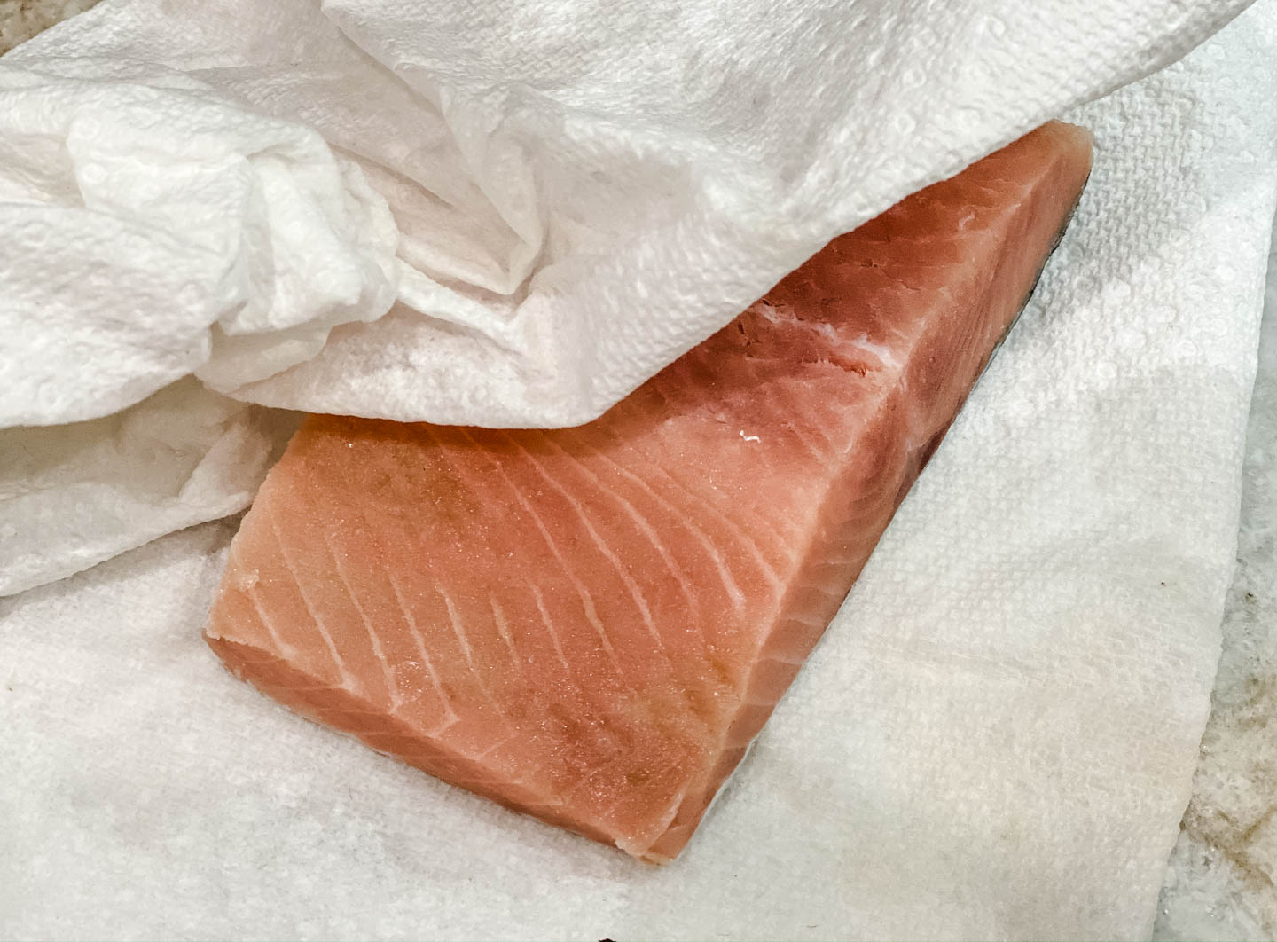 Raw salmon sitting on paper towels.