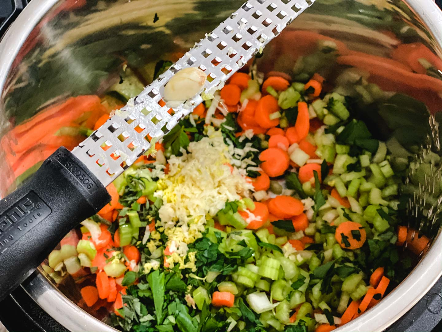 Chopped carrots, celery, parsley, sage, ginger and garlic in a steel pot in a grater on top.
