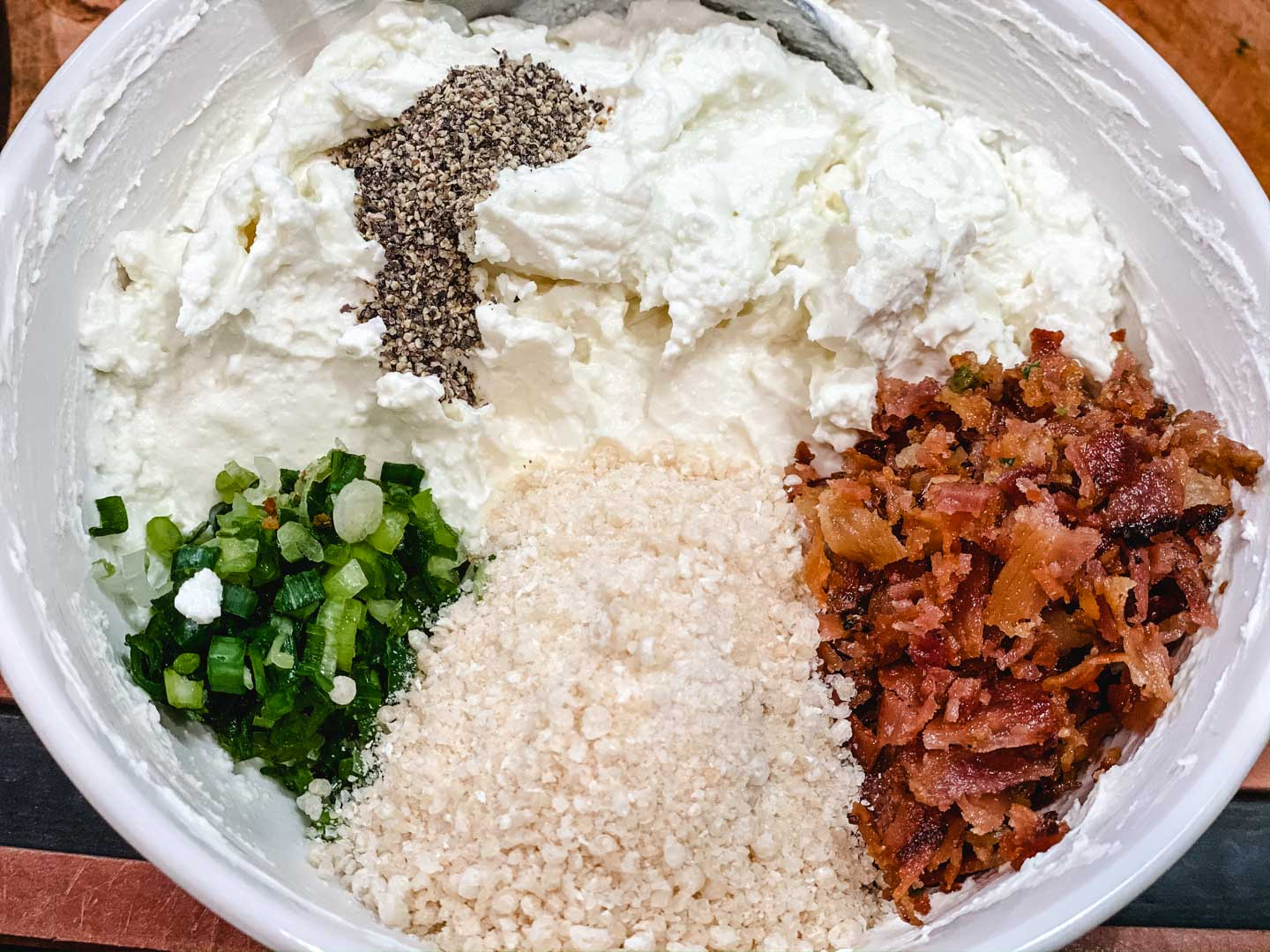 Goat cheese, cream cheese, bacon, spring onion, breadcrumbs and pepper in a white bowl