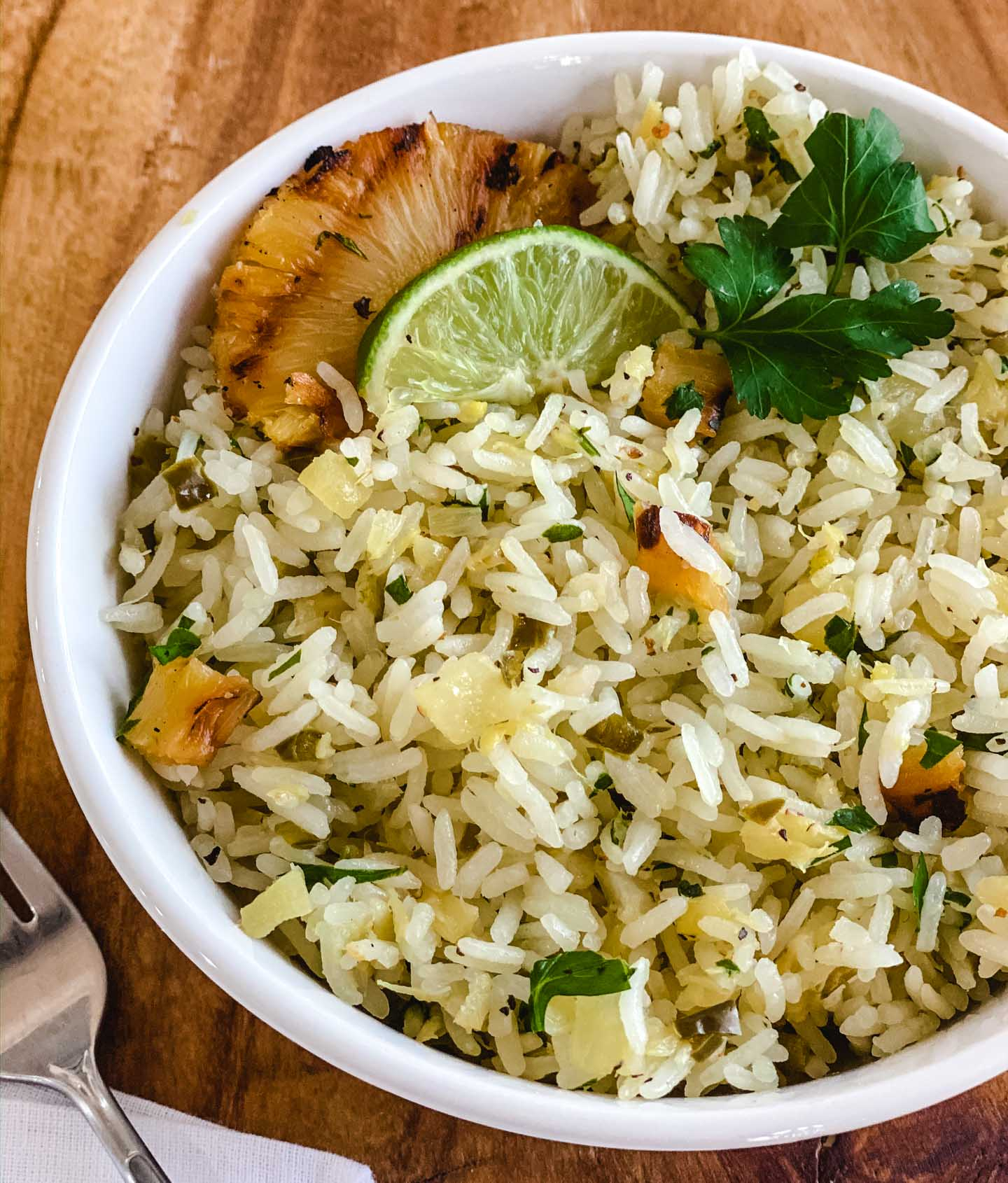 Rice in a white bowl with grilled pineapple, jalapenos, lime and parsley