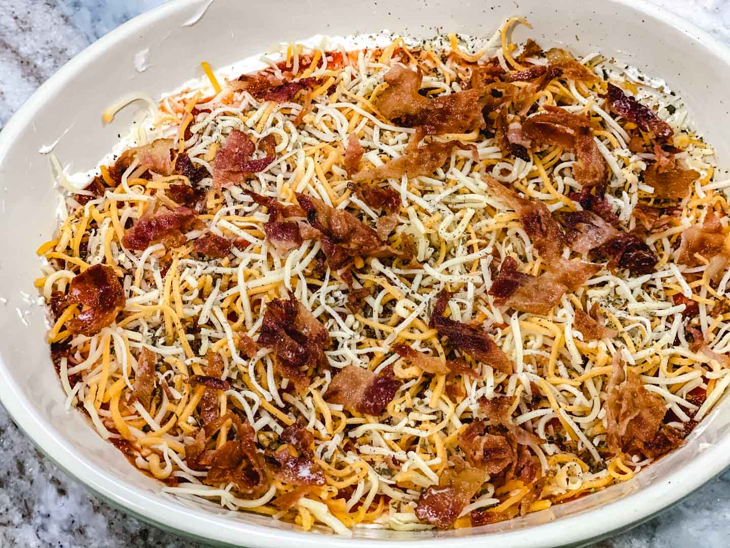 Shredded cheese with bacon in a white bowl on a counter.