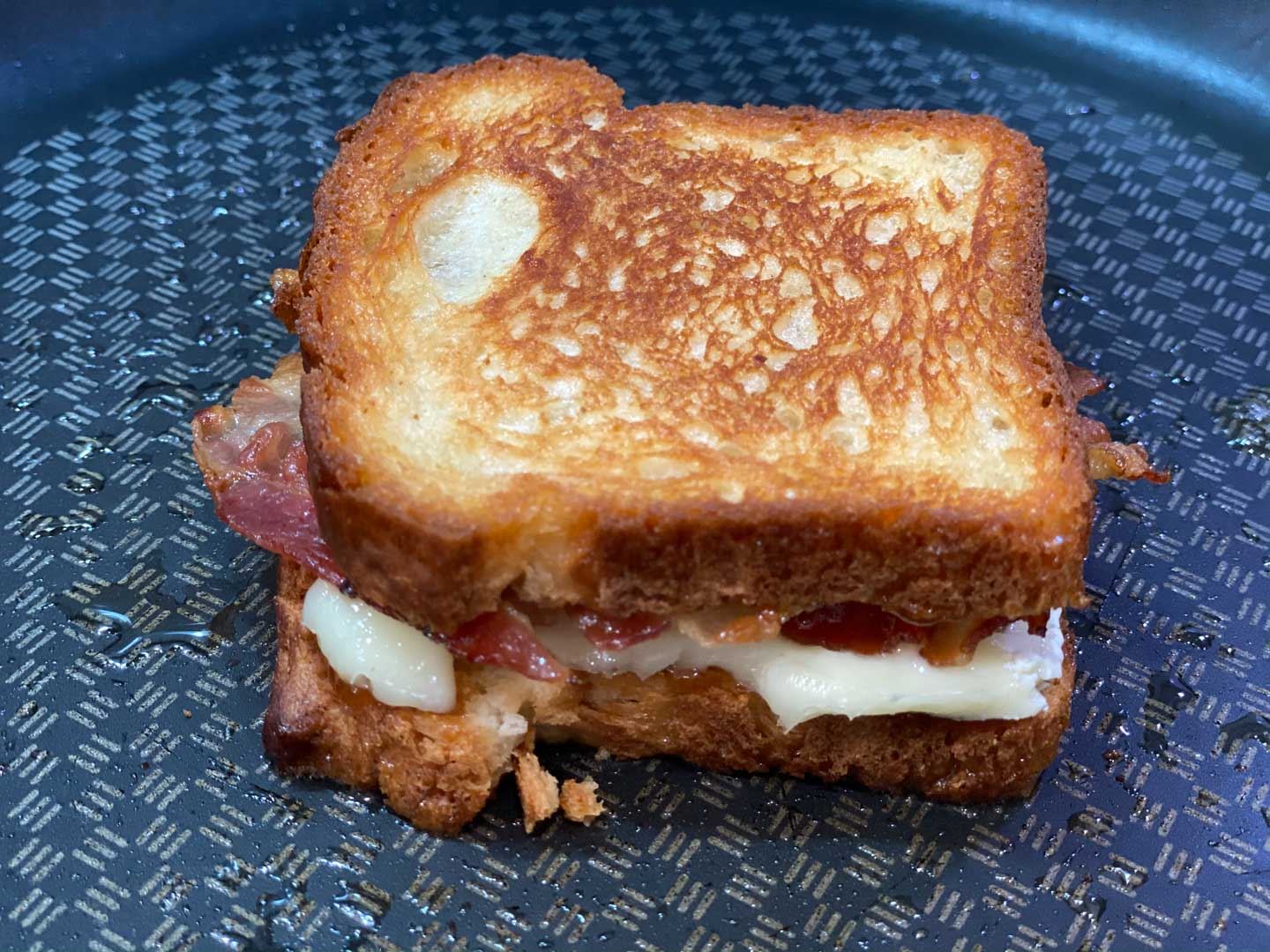 Grilled cheese in a saute pan with fig spread, brie, and bacon.