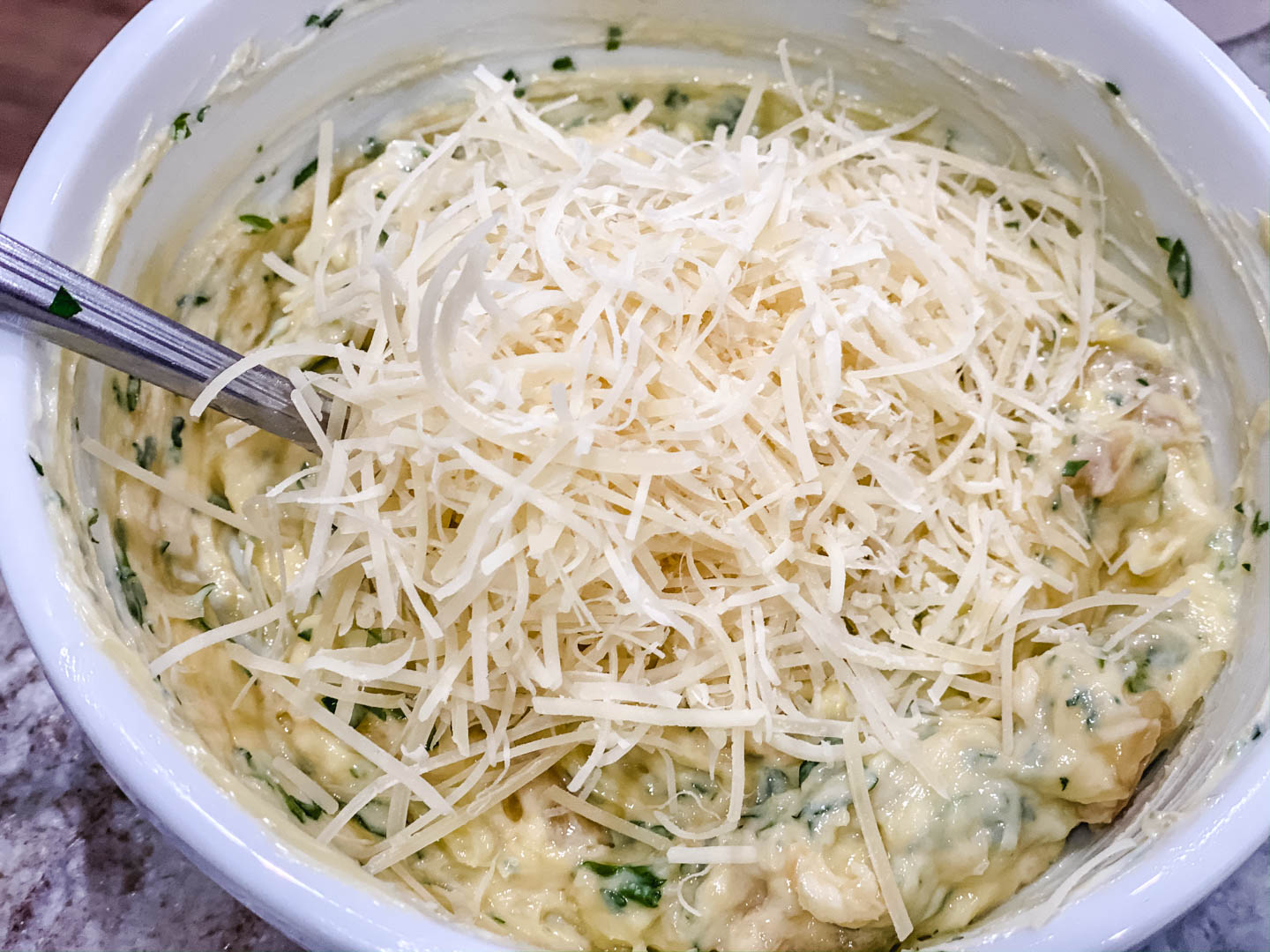 Butter, mayo. parsley, roasted garlic in a white bowl with parmesan cheese on top.