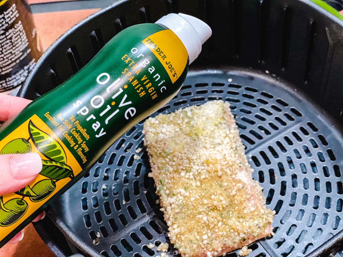 Crusted salmon in an air fryer with a bottle of olive oil spray.