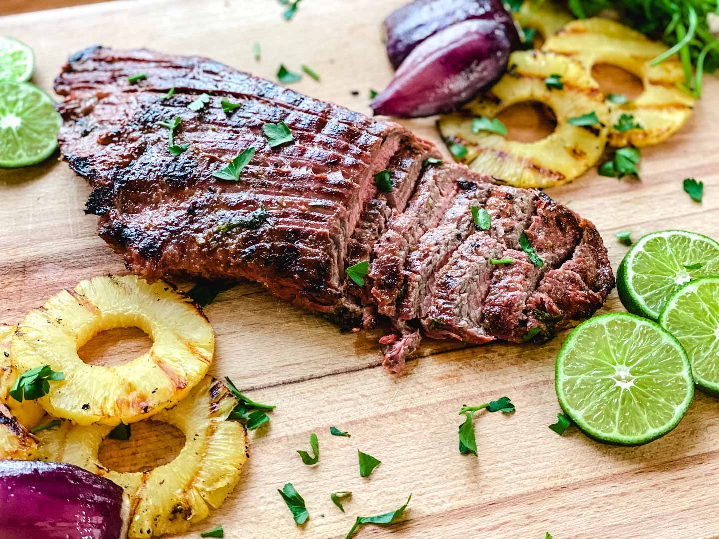Steak on a wood board with limes, pineapples, red onions and parsley.