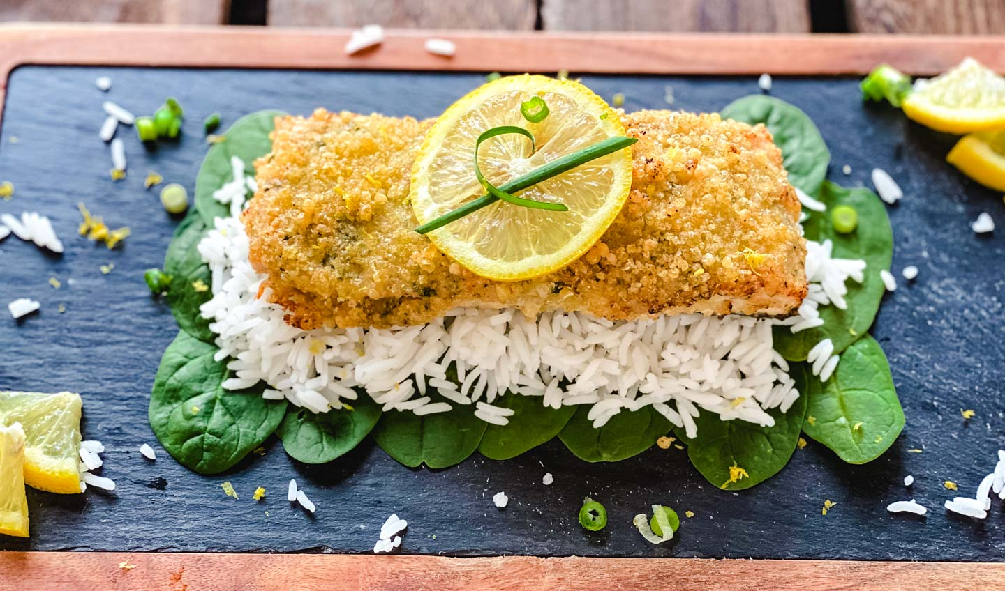 Crusted salmon on rice and spinach leaves with lemons on a cutting board.