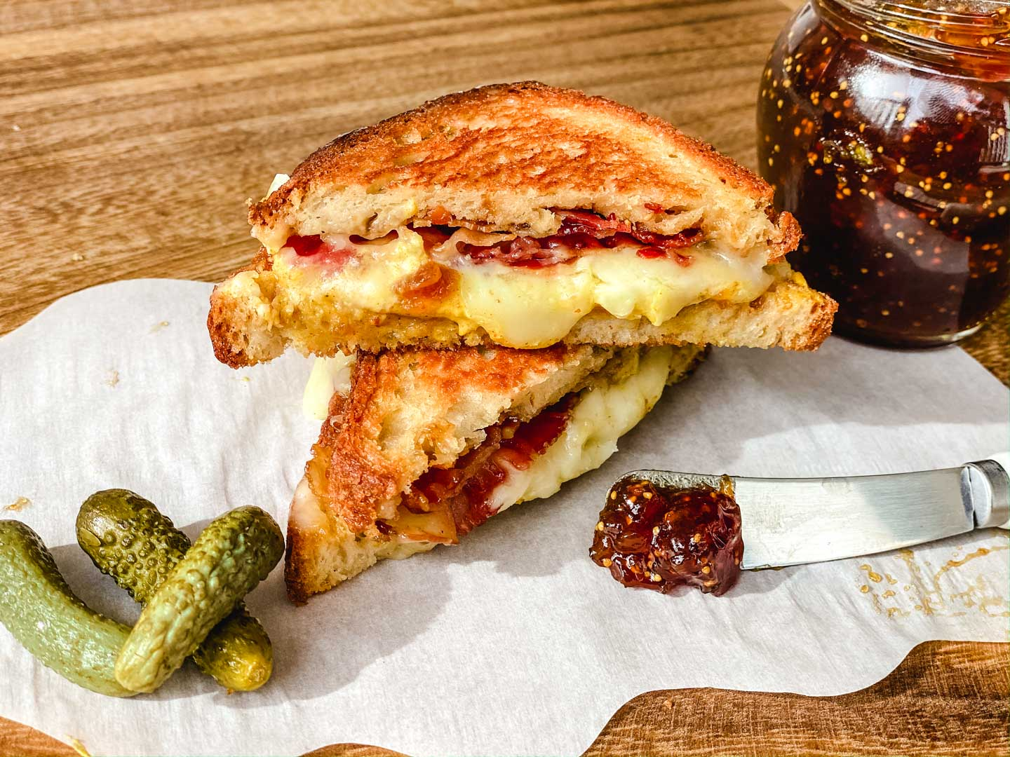 Grilled cheese with a jar of fig spread with pickles off to the side.