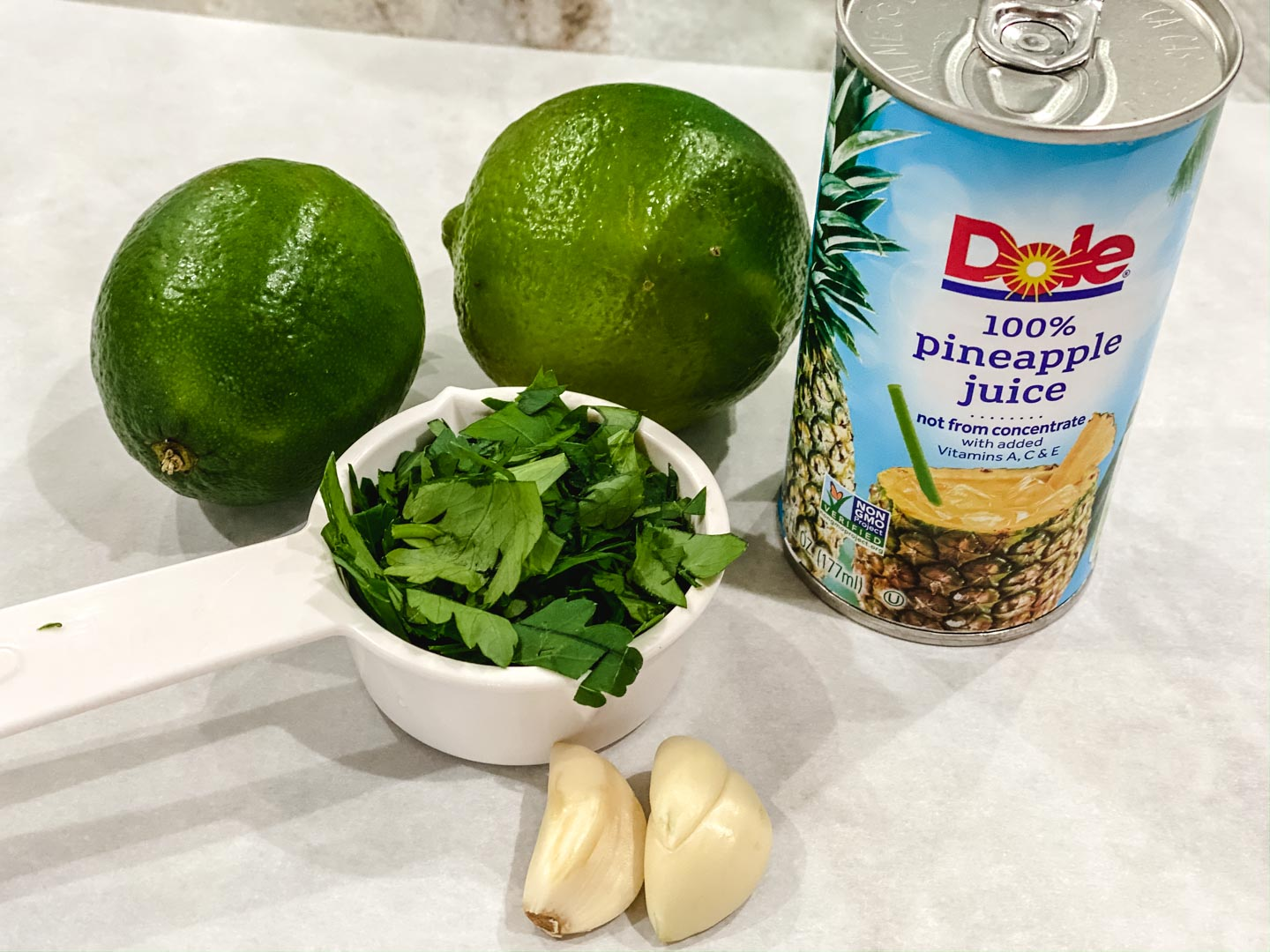 Limes, parsley, pineapple juice and garlic on parchment paper.
