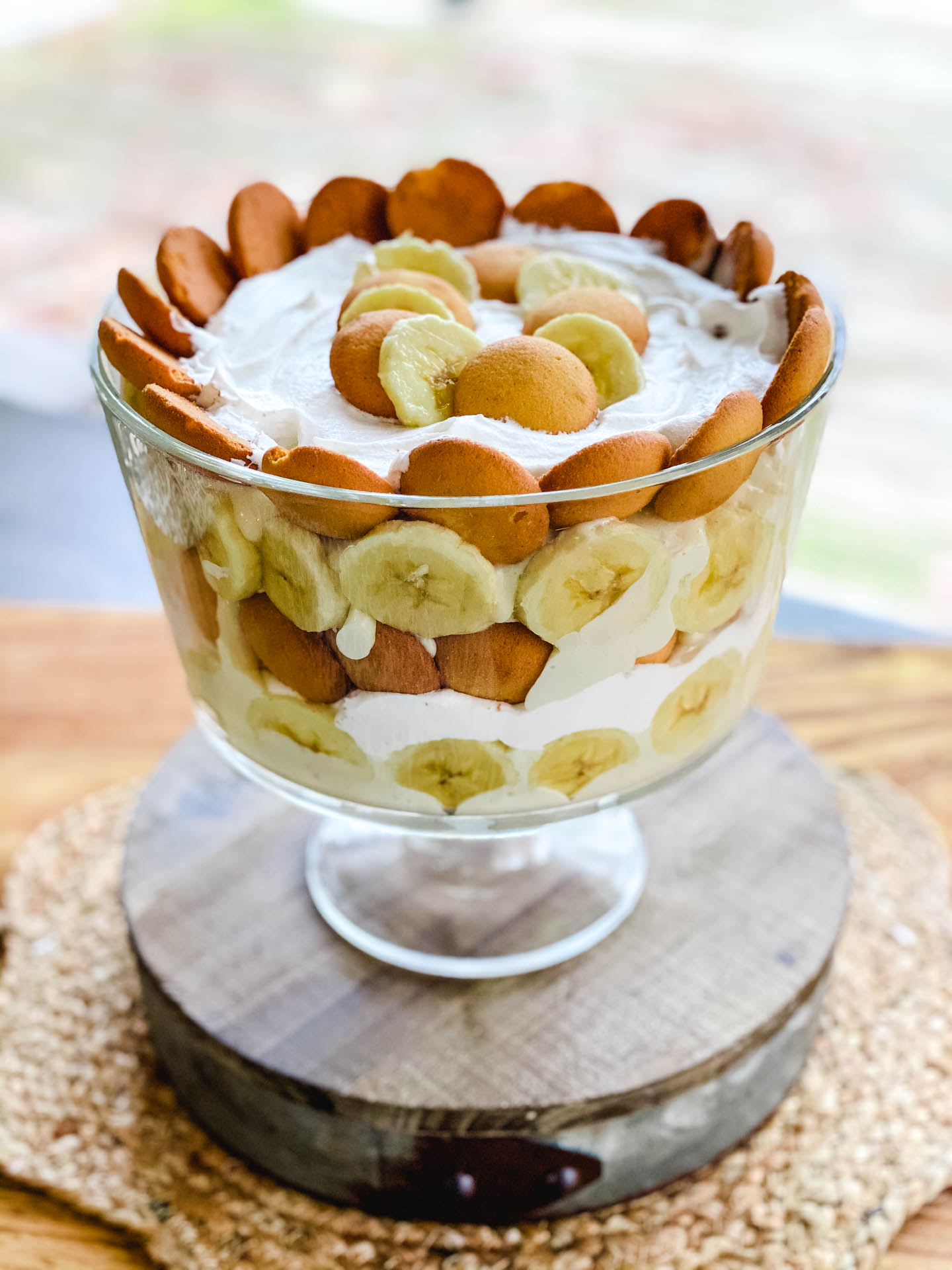 Bananas, pudding, whipped cream, and cookies in a glass bowl on a brown stand.
