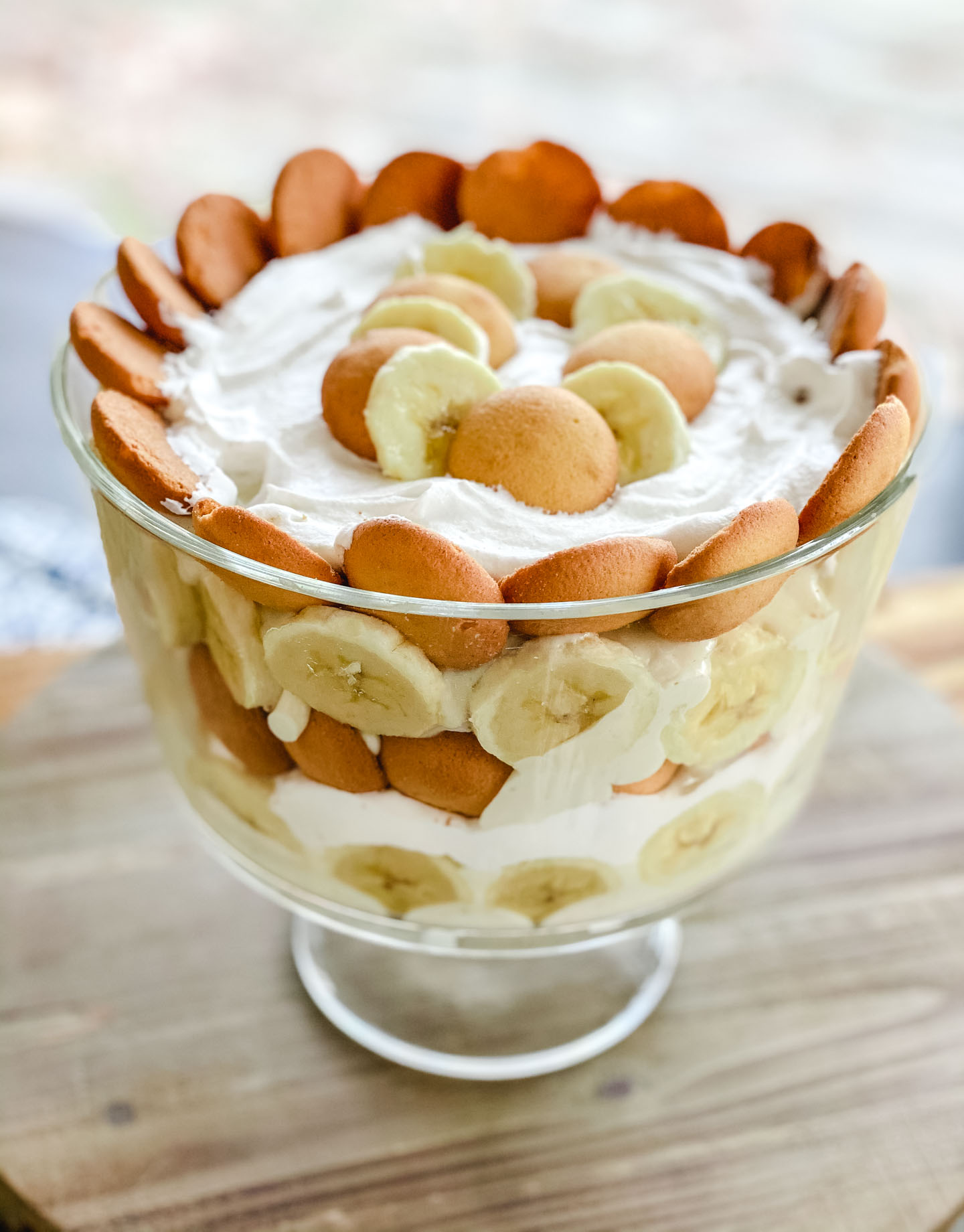 Bananas, cookies, pudding, and whipped cream in a glass bowl