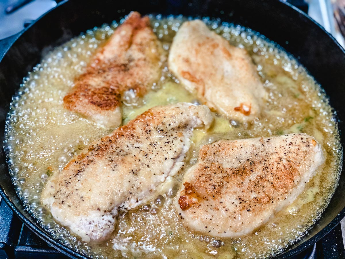 Chicken cooking in a skillet with sauce.