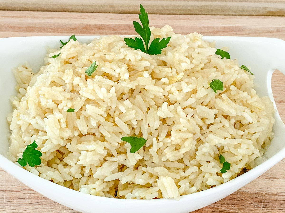 Rice in a white bowl sprinkled with parsley