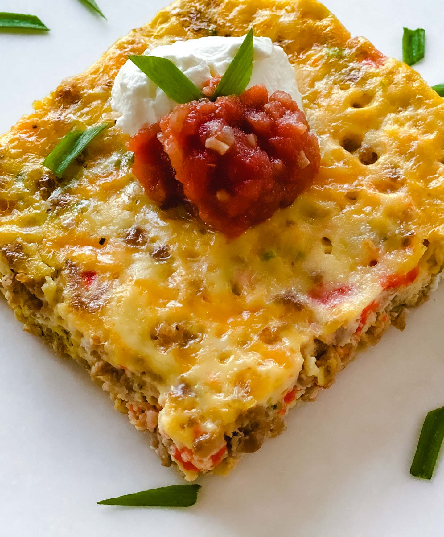 Egg casserole with salsa, sour cream,  green onions, red peppers, and cheese sitting on a white plate.
