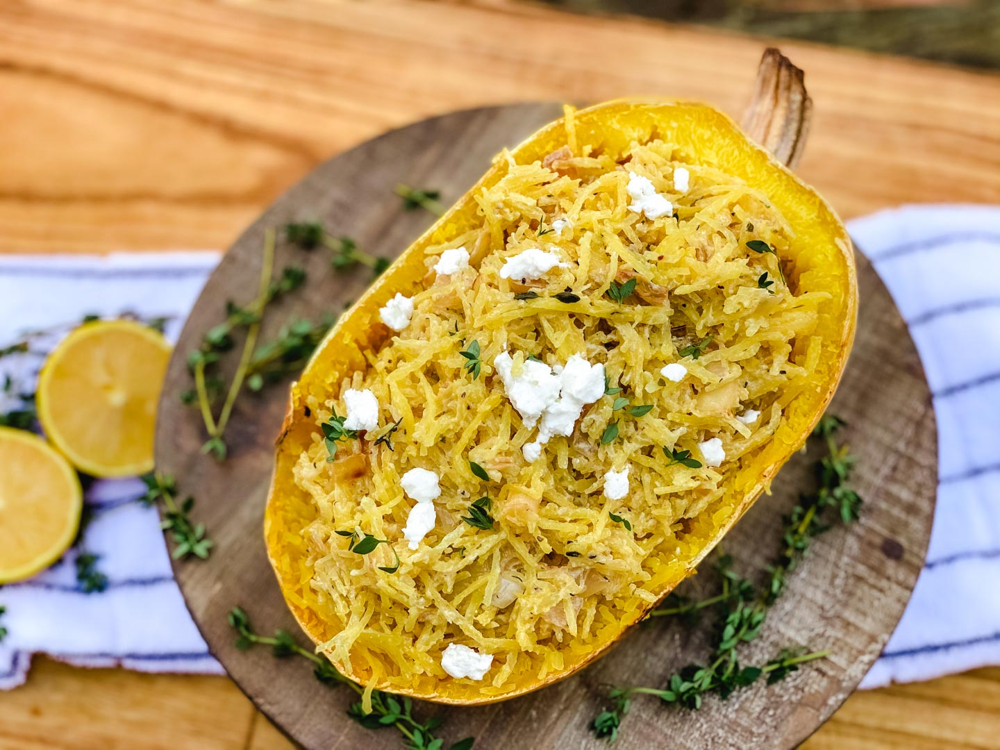 Spaghetti squash sitting on a wood board with fresh thyme.