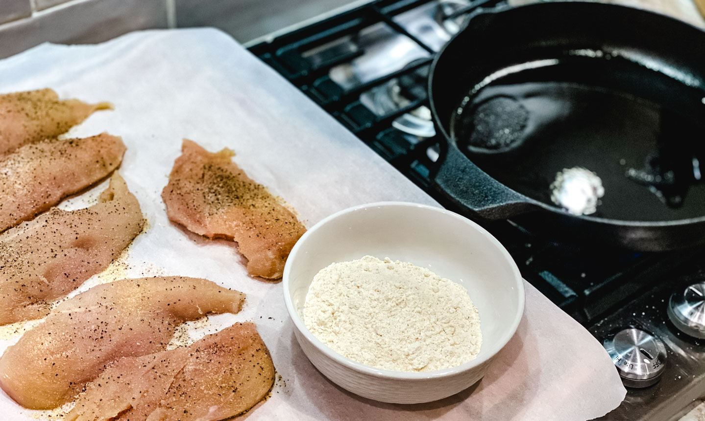 Raw chicken on parchment paper with seasonings along with a bowl of flour and cast iron skillet on a stove.