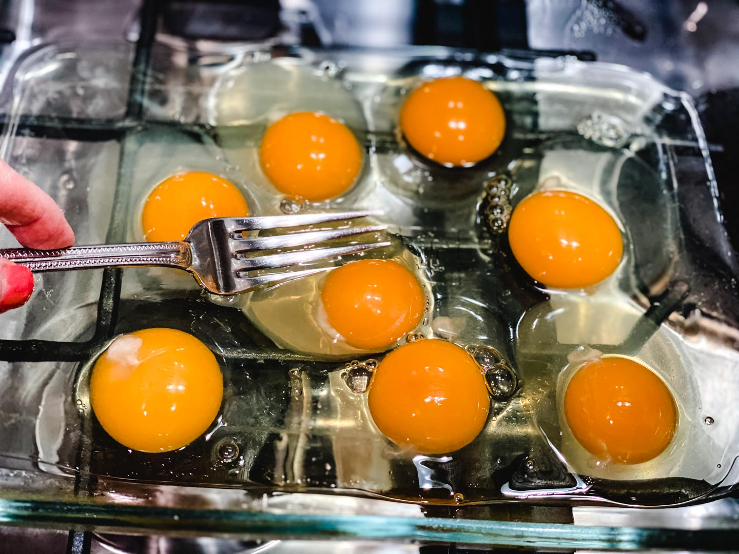 Baking dish with 8 eggs and a fork.