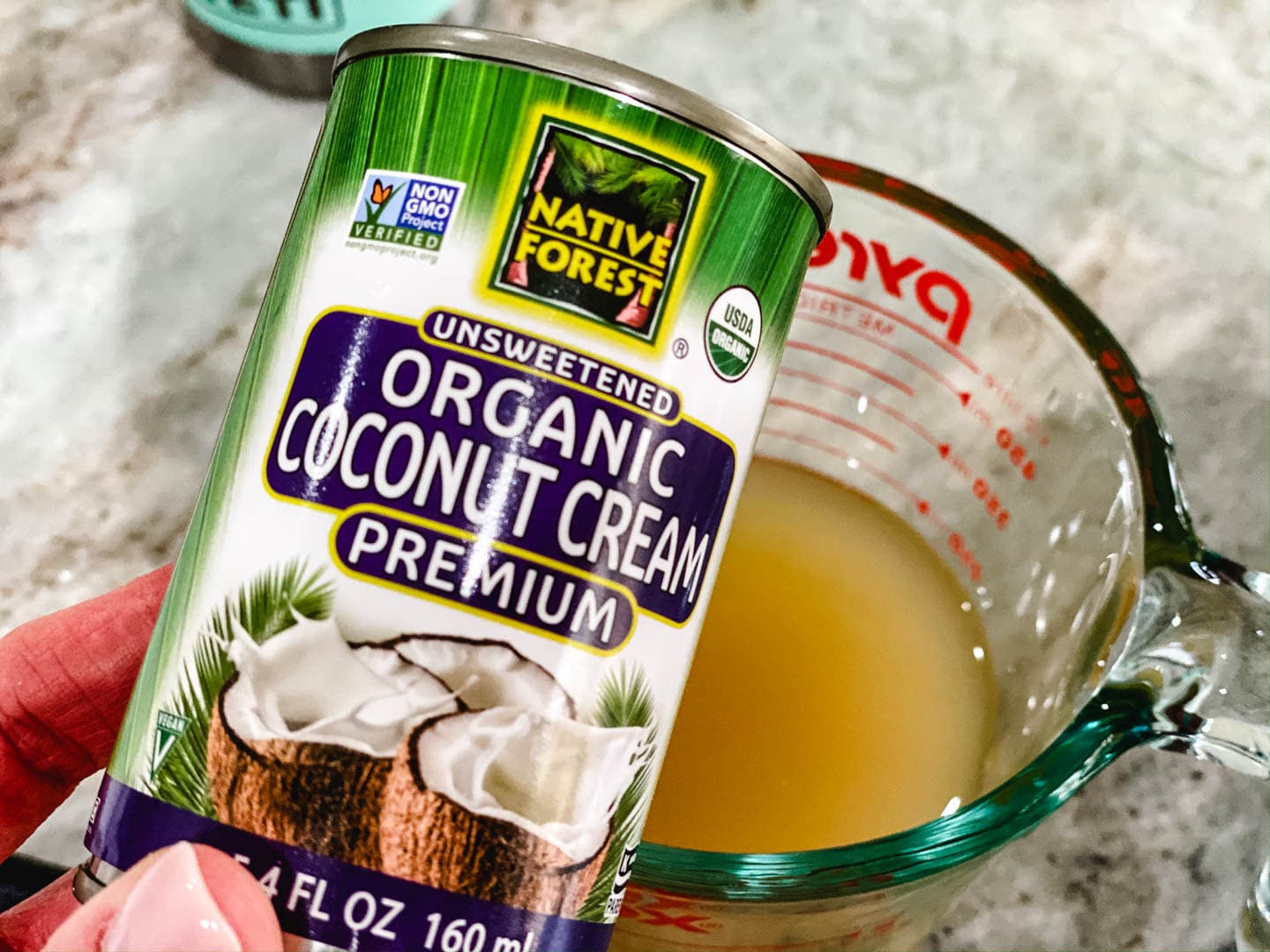 Can of coconut cream with a cup of chicken broth in the background.