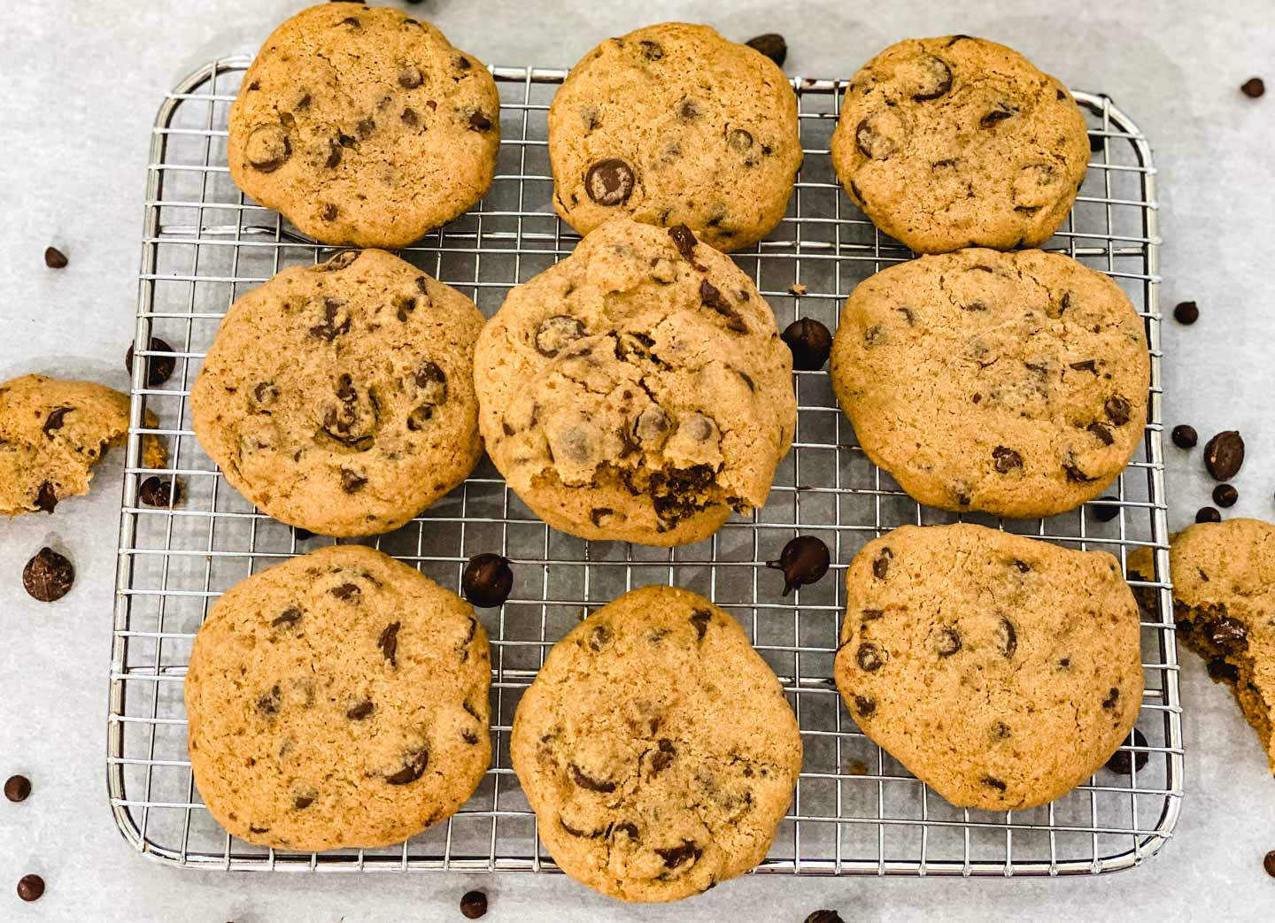 Fresh baked gluten free chocolate chip cookies on a cooling rack with parchment paper underneath them.