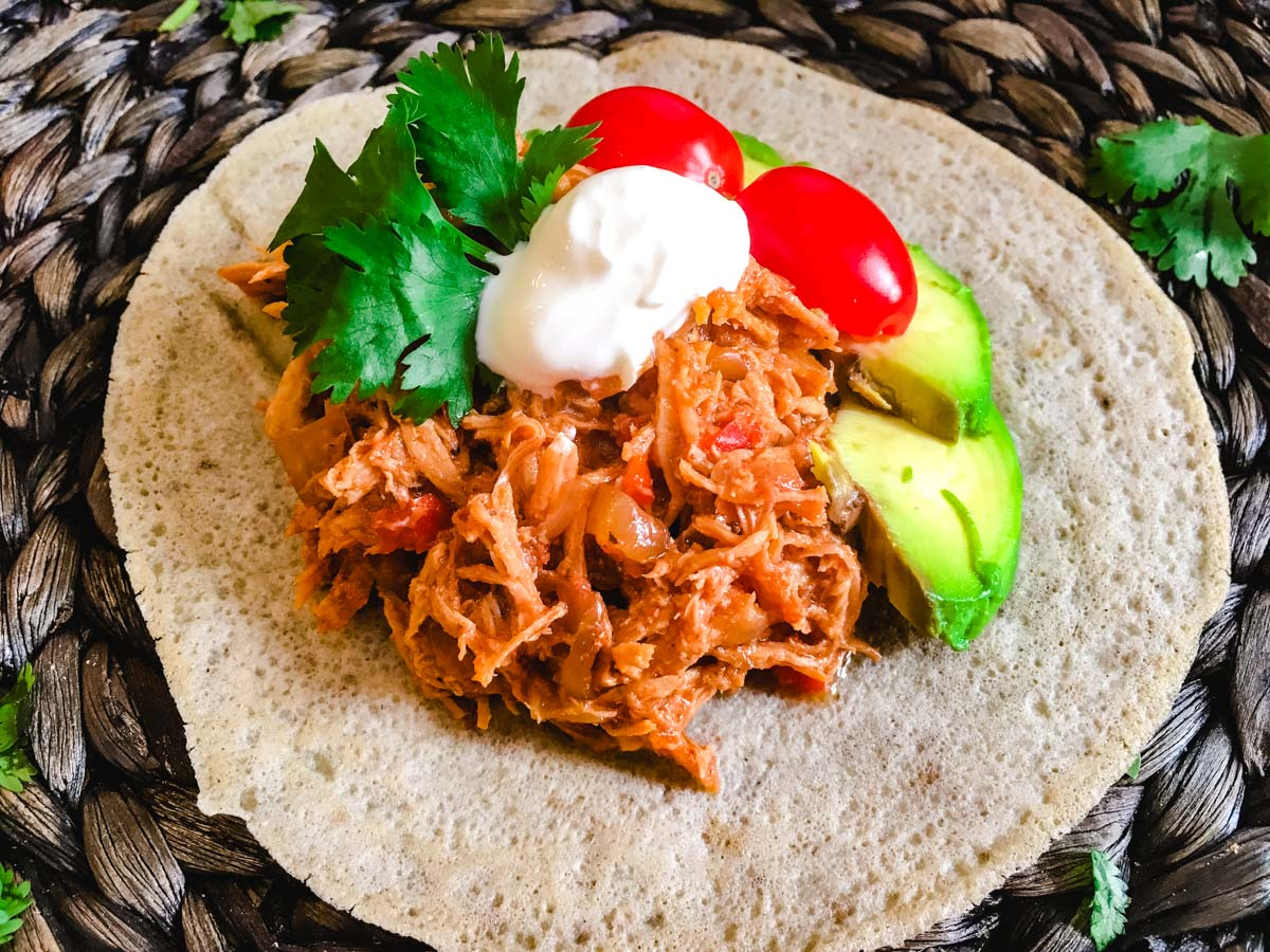 Pulled BBQ chicken on a tortilla with avocado, tomato, and a dollop of sour cream!