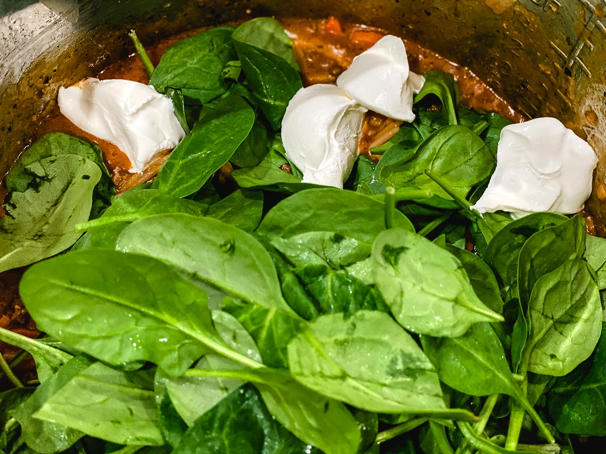 Fresh spinach, cream cheese and pasta sauce in an Instant Pot.