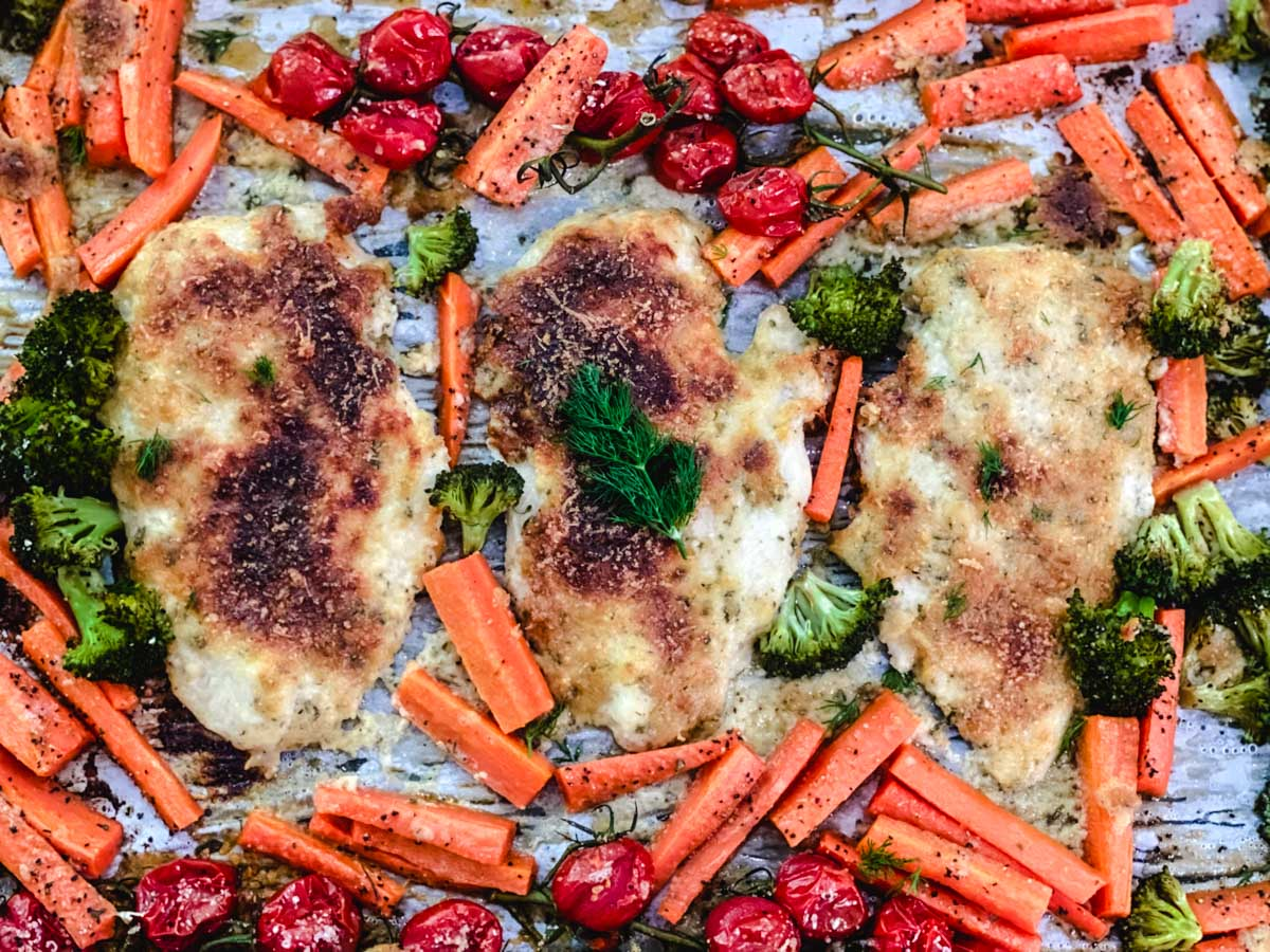 Cooked chicken on a pan with carrots, tomatoes, and broccoli.