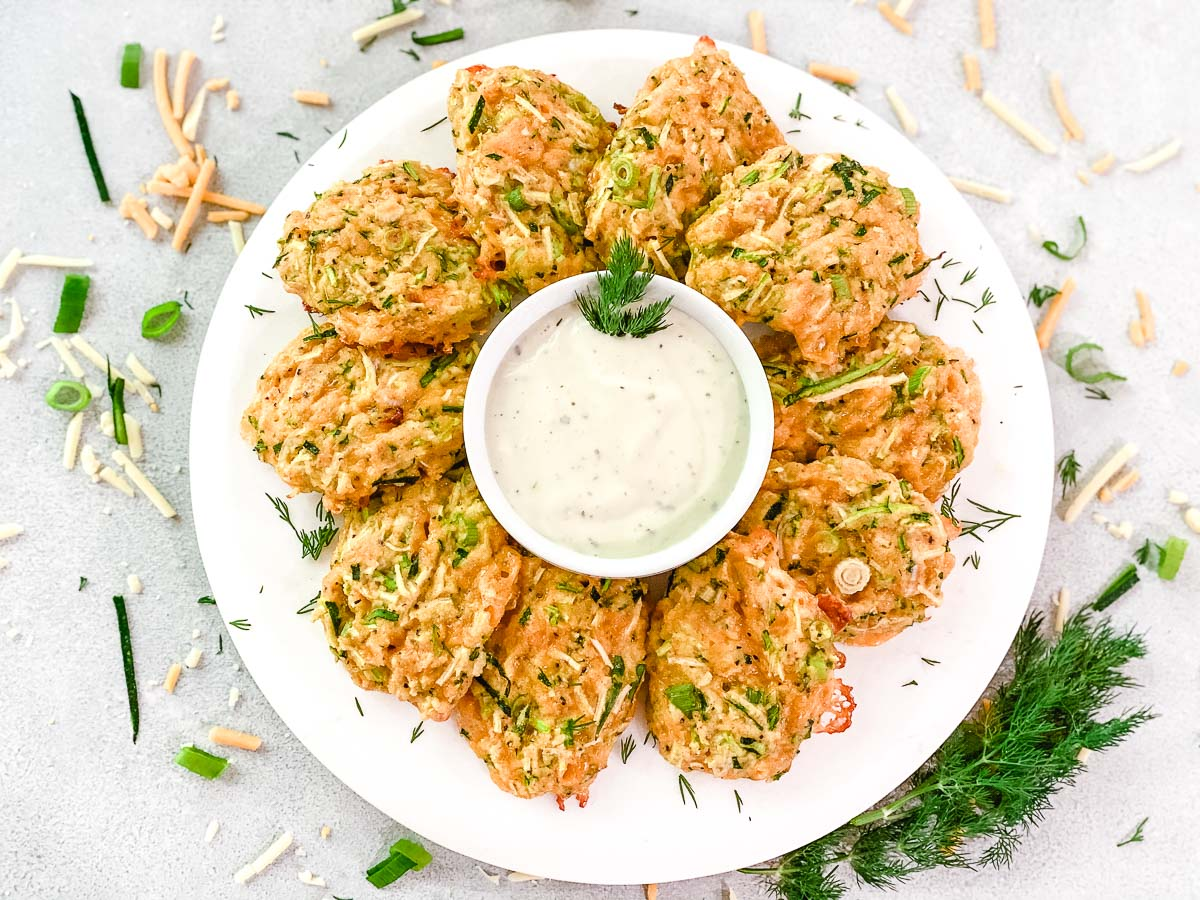 Zucchini Bites on a white plate with ranch dressing.