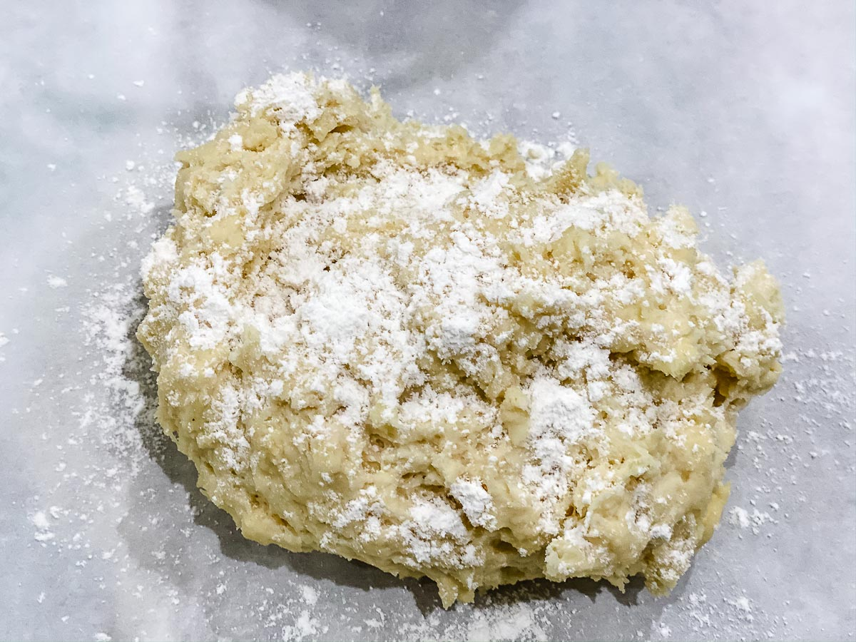 Dough with flour sprinkled on top in a white bowl.