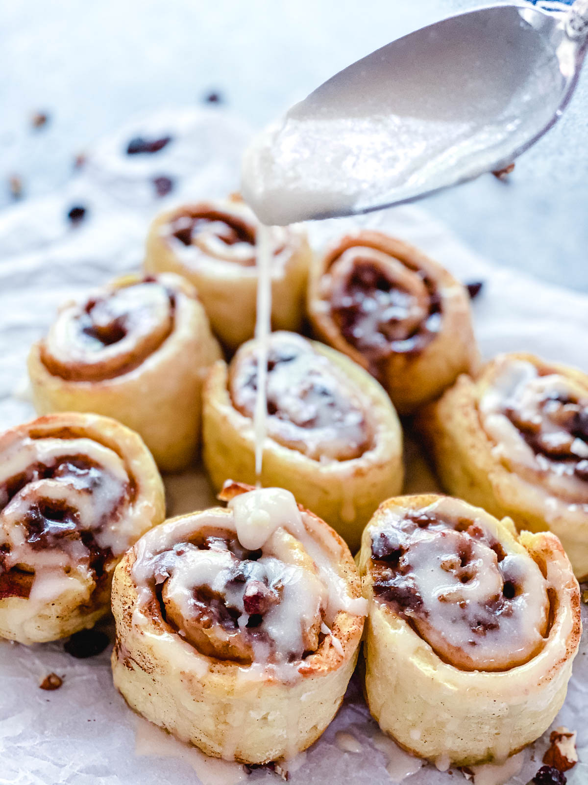 Cinnamon rolls with glaze being drizzled on top.