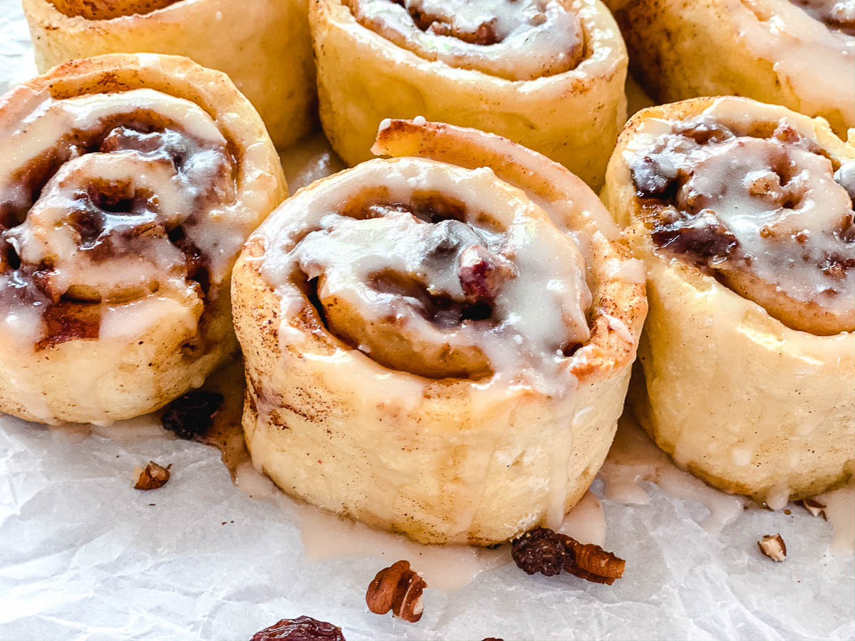 Cinnamon rolls with icing and pecans and raisins.