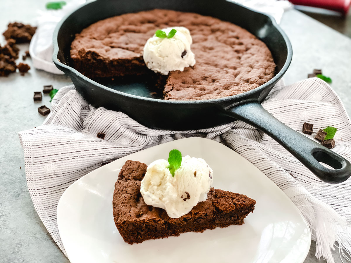 Fudge Cookie Pie in a skillet with a slice off to the side, topped with vanilla ice cream.