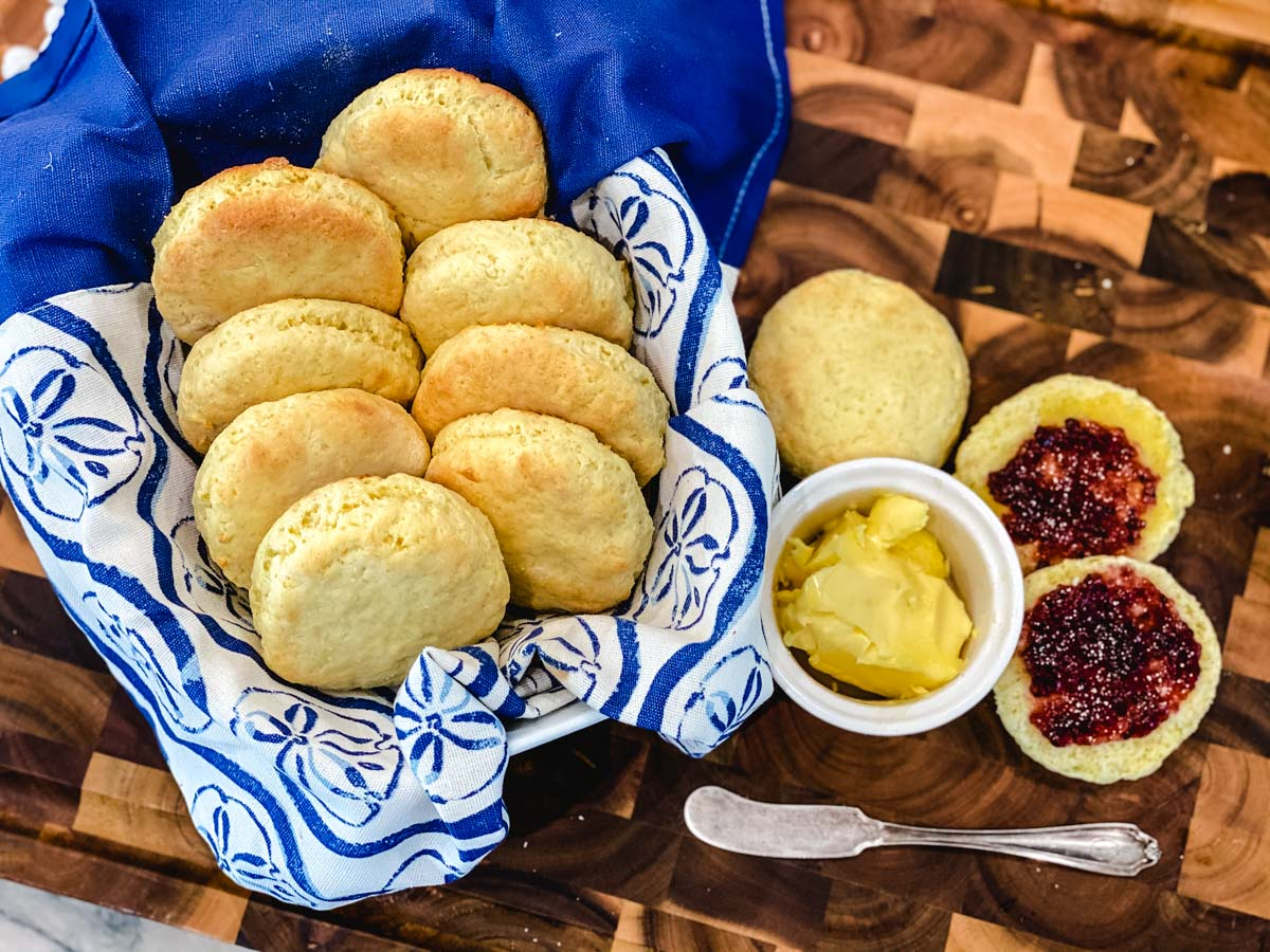 Gluten free biscuits in a basket with butter, jam and more biscuits off to the side.