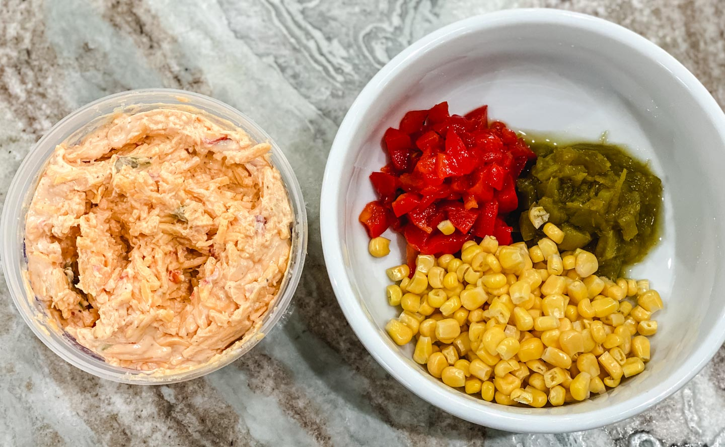 Bowl of pimento cheese and a bowl or corn, red peppers and green chilis.